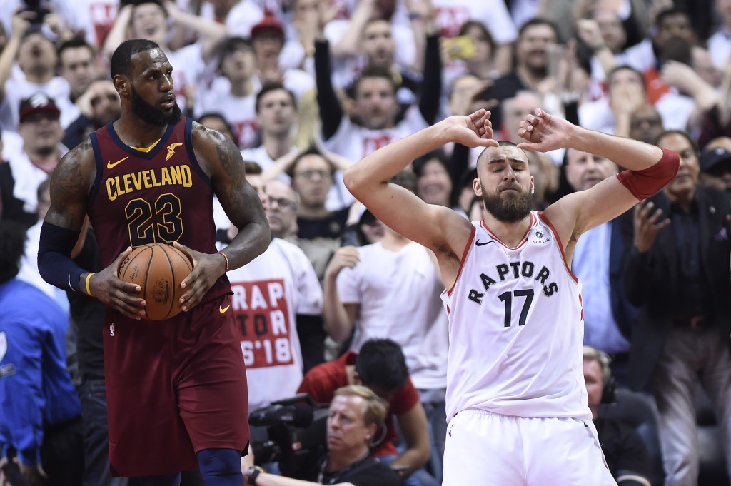 Toronto Raptors center Jonas Valanciunas (17) reacts after missing a shot late in the second half as Cleveland Cavaliers forward LeBron James (23) hol...