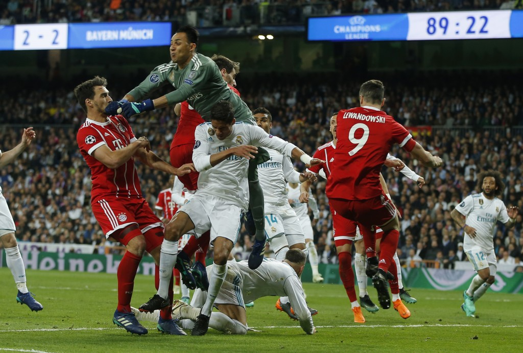 Real Madrid's goalkeeper Keylor Navas, top, deflects a ball during the Champions League semifinal second leg soccer match between Real Madrid and FC B...