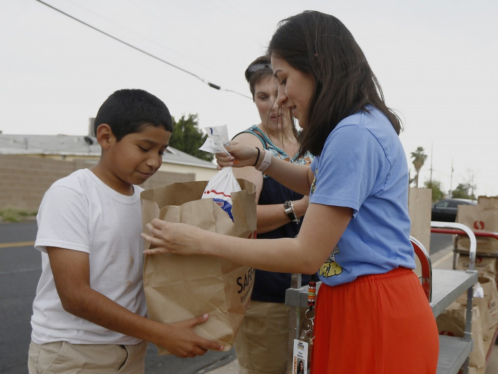 Erica Martinez, right, a teacher at Webster Elementary School, hands out a free food bag to one of her students as the teachers donated over 200 food ...