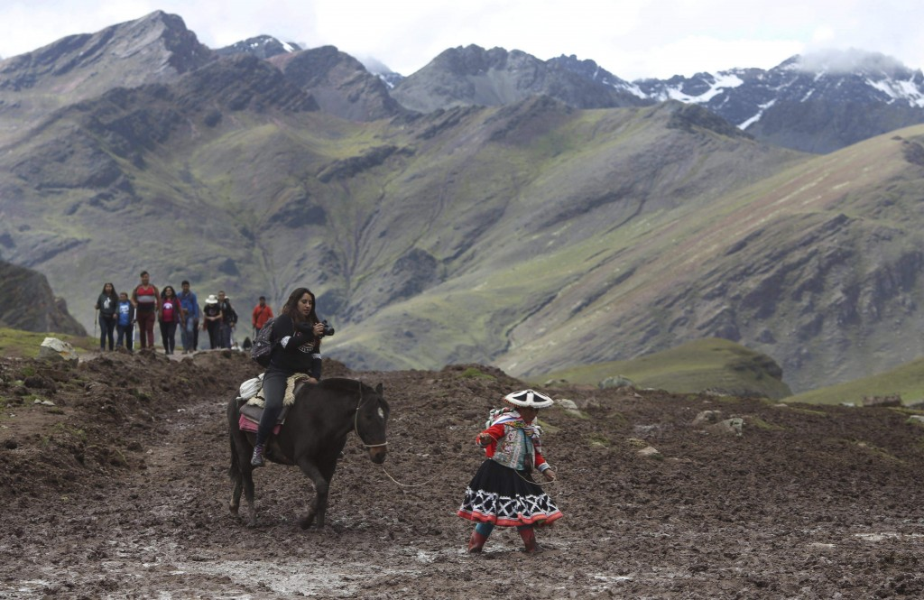 In this March 2, 2018 photo, a group of tourists ride horses led by an Andean guide to Rainbow Mountain, a ridge of multicolored sediments laid down m...