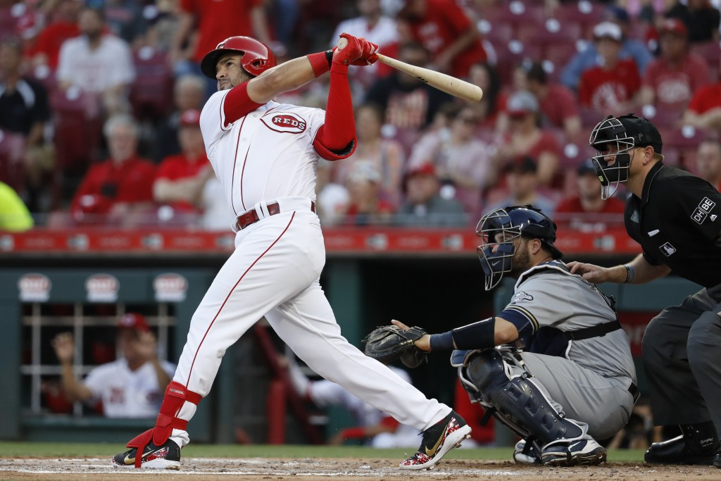 Cincinnati Reds' Eugenio Suarez hits a two-run home run off Milwaukee Brewers starting pitcher Chase Anderson during the first inning of a baseball ga...