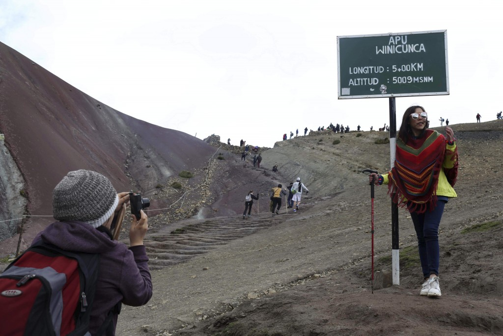 In this March 2, 2018 photo, a tourist poses for a photo at the entrance that leads to Rainbow Mountain, in Pitumarca, Peru. Backpackers are flocking ...