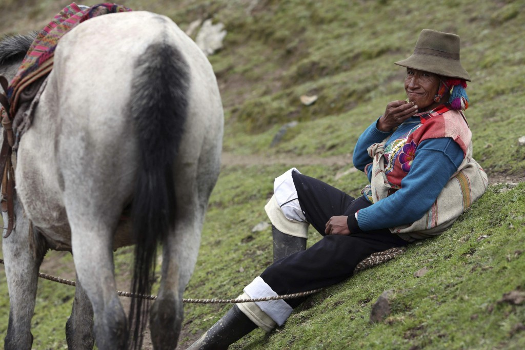 In this March 2, 2018 photo, an Andean muleteer rests during a break from guiding tourists to Rainbow Mountain, in Pitumarca, Peru. The 16,404-foot (5...