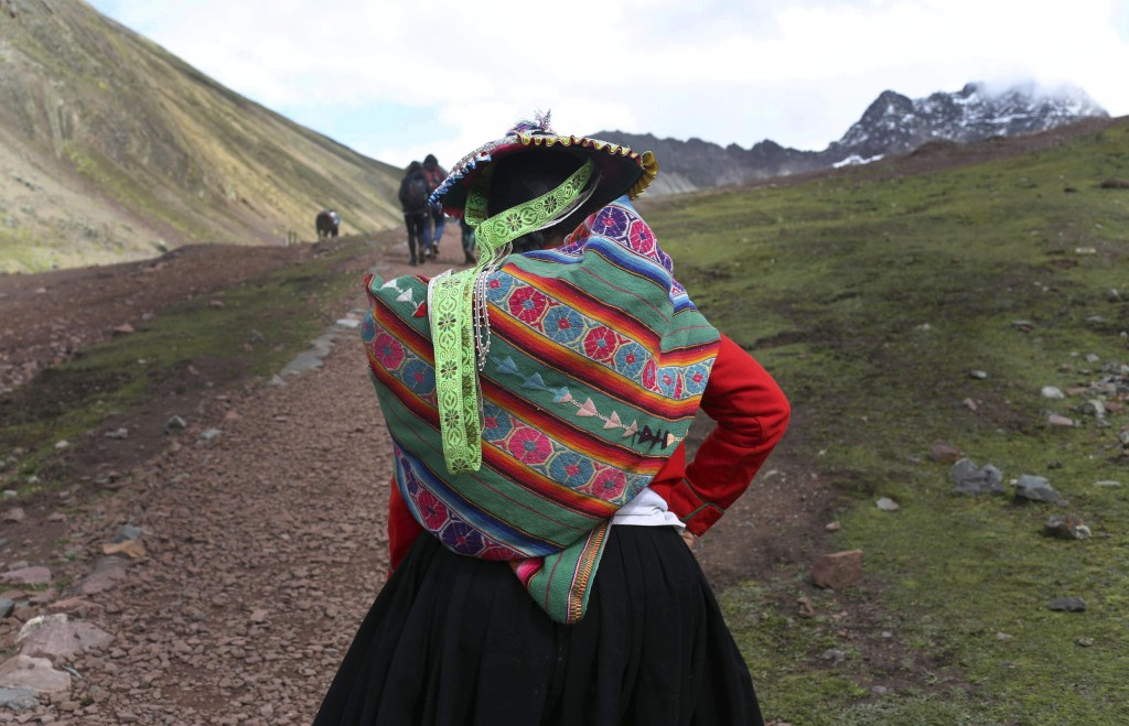 In this March 2, 2018 photo, an Andean woman walks to Rainbow Mountain in Pitumarca, Peru. The 16,404-foot (5,000-meter) peak of multicolored sediment...