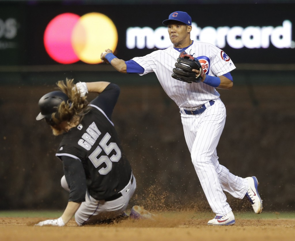 Chicago Cubs' Addison Russell, right, turns the double play, throwing to first after forcing out Colorado Rockies' Jon Gray (55) at second, to get Cha...