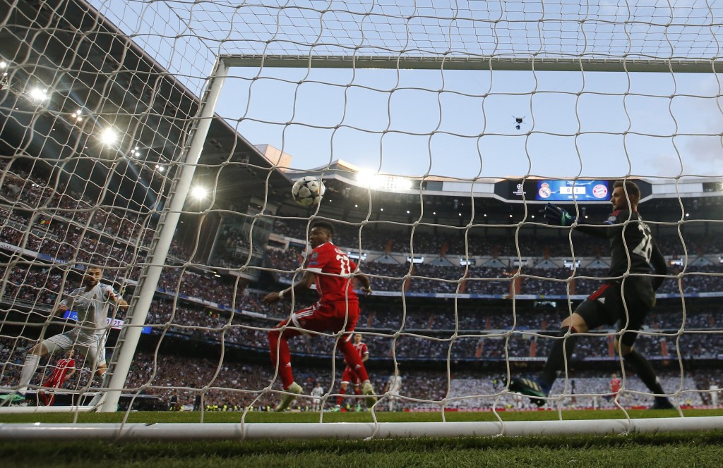 Real Madrid's Karim Benzema, left, scores his side's opening goal past Bayern's David Alaba, center, and goalkeeper Sven Ulreich during the Champions ...