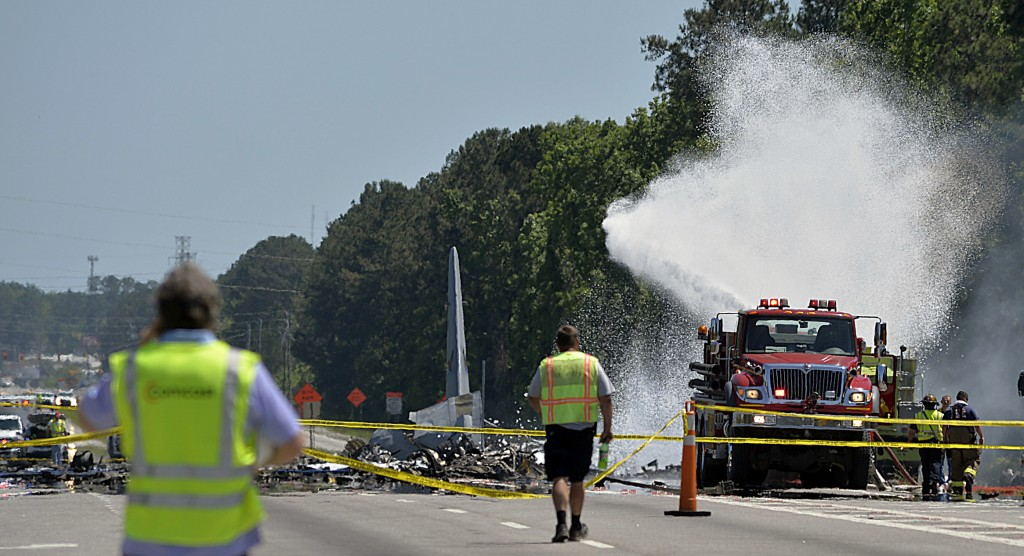 A firetruck sprays foam over the remains of an Air National Guard C-130 cargo plane from Puerto Rico that crashed near the intersection of state highw...