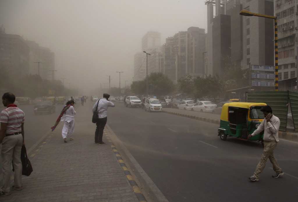In this Wednesday, May 2, 2018 photo, people cross a road, enveloped by dust rising from a storm in New Delhi, India. A powerful dust storm and rain s...