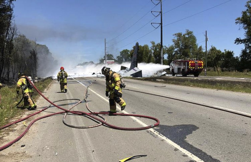 This photo made available by the Chatham Emergency Services, GA., shows firefighters putting out a fire caused by a plane crash near the airport in Sa...