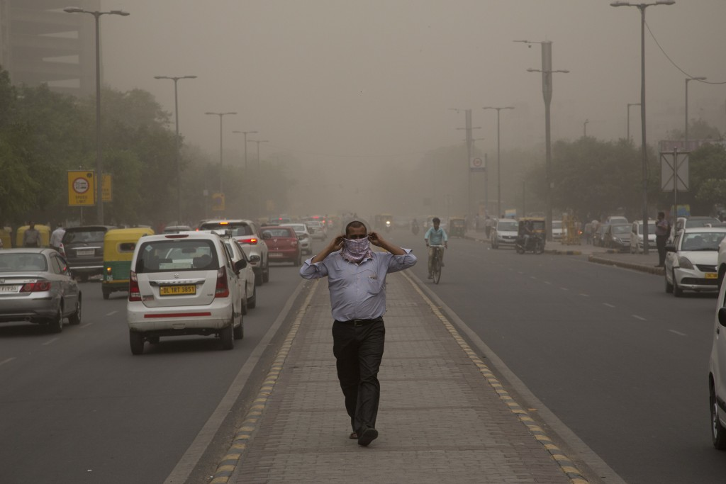 FILE - In this Wednesday, May 2, 2018, file photo, a man wraps a scarf around his nose as a dust storm envelops the city in New Delhi, India. Official...