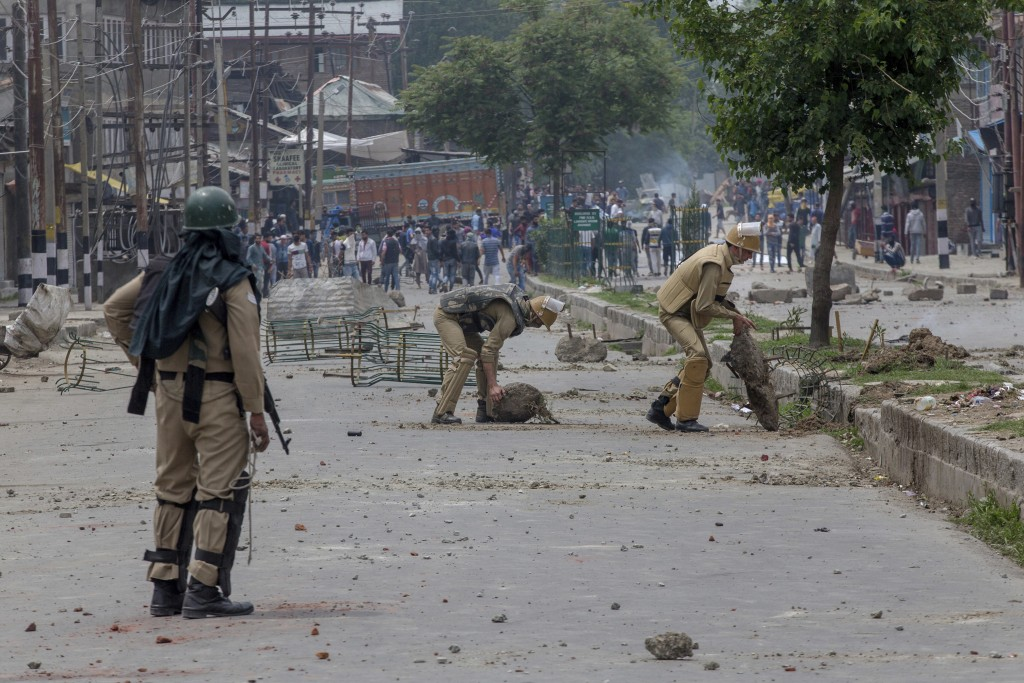 Indian policemen remove rocks, set up as barricade by Kashmiri protesters, near the site of a gun battle in Srinagar, Indian controlled Kashmir, Satur...