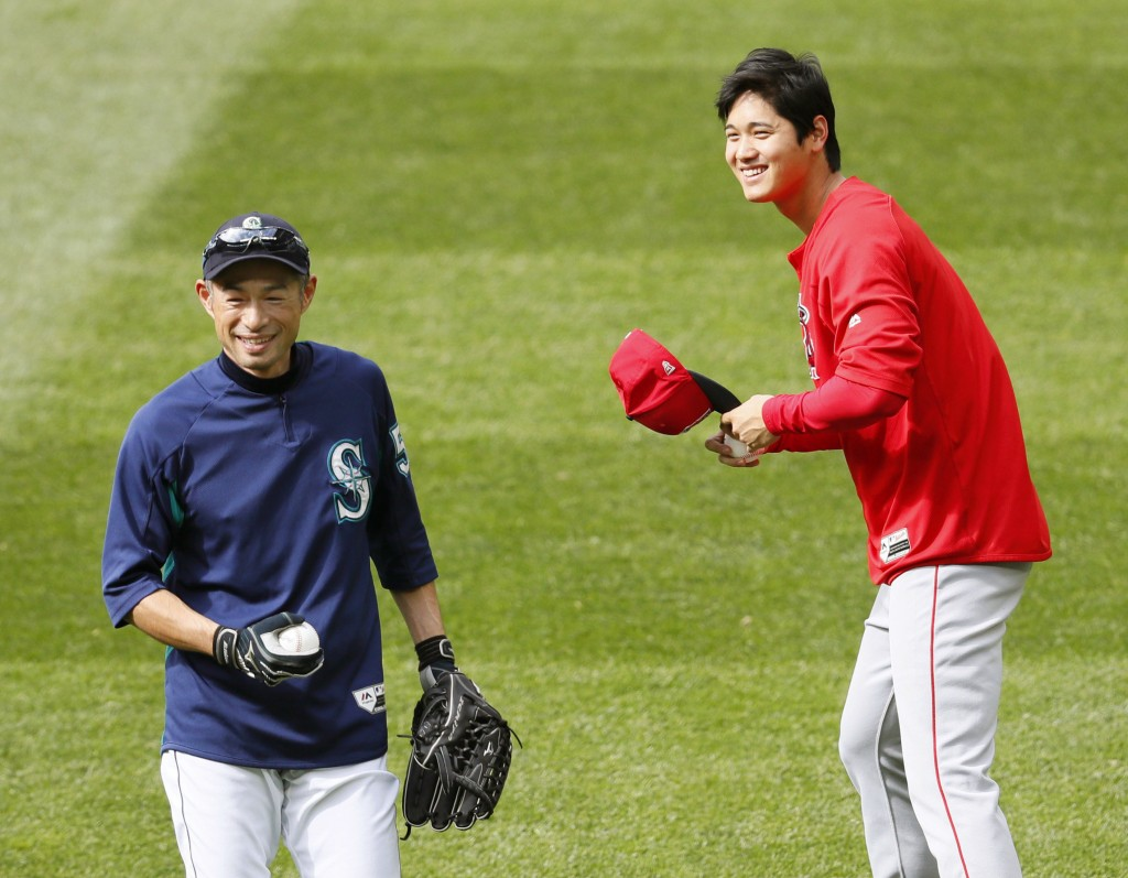 Los Angeles Angels' Shohei Ohtani, right, and former Seattle Mariners outfielder Ichiro Suzuki, left, share a light moment during a practice session F...