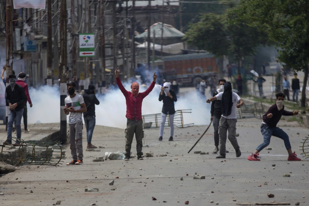 Kashmiri protesters throw rocks and bricks at Indian paramilitary soldiers near the site of a gun battle in Srinagar, Indian controlled Kashmir, Satur...