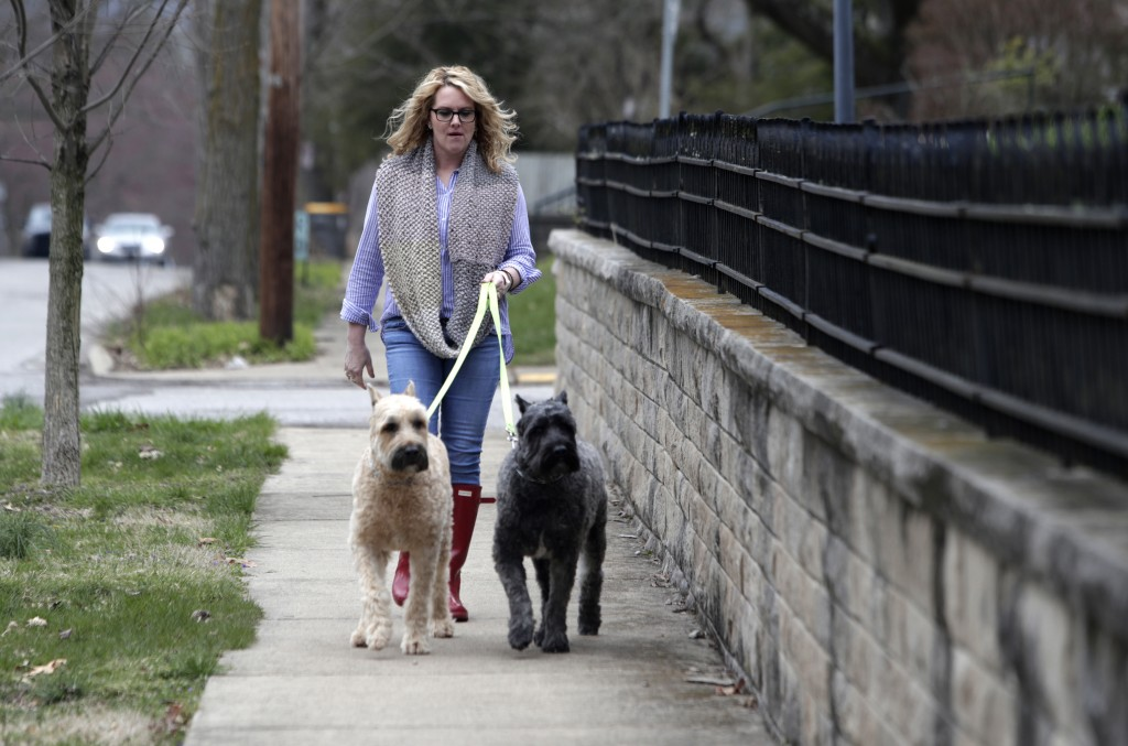 In this Monday, April 9, 2018, photo, Angela Ricketts walks her dogs in Bloomington, Ind. Russian spies masqueraded as Islamic State supporters to thr...