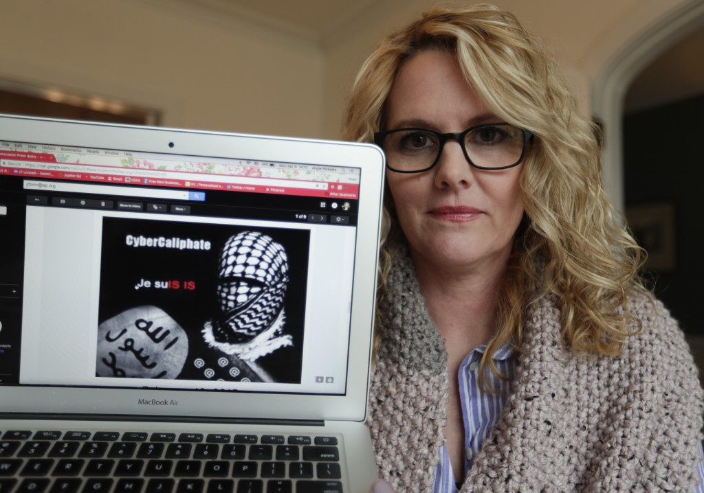 In this Monday, April 9, 2018, photo, Angela Ricketts poses with a screen shot of a message she received from a group claiming to be Islamic State sup...