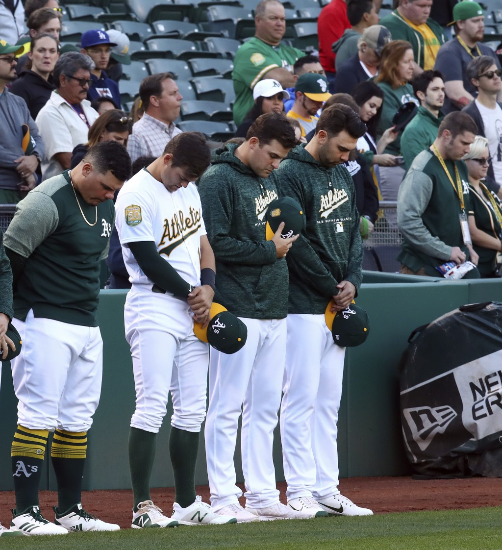 Oakland Athletics including Bruce Maxwell, left, bow their heads in memory of Gretchen Piscotty, mother of right fielder Stephen Piscotty, prior to a