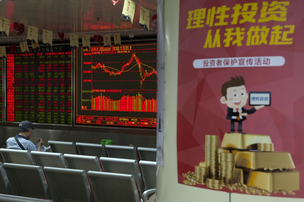 """An investor eats his meal as he monitors stock prices near a poster which reads """"Rational investing starts from me"""" at a brokerage in Beijing, China, ..."""