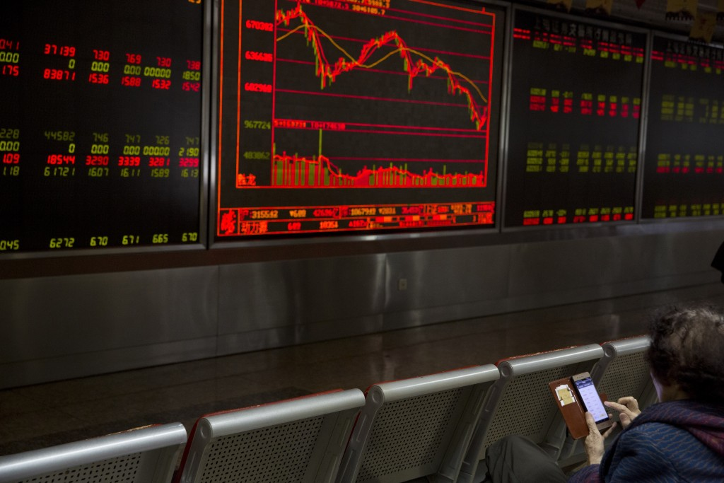 An investor monitors stock prices at a brokerage in Beijing, China, Wednesday, May 9, 2018. Oil prices surged while Asian stock markets traded mixed a...