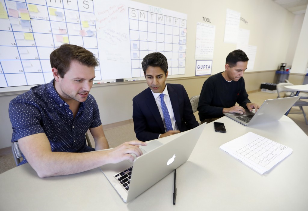 In this Tuesday, May 1, 2018, photo, Suneel Gupta, center, works with campaign manager Michael Kurtz, left, and finance associate Michael Flores at hi...