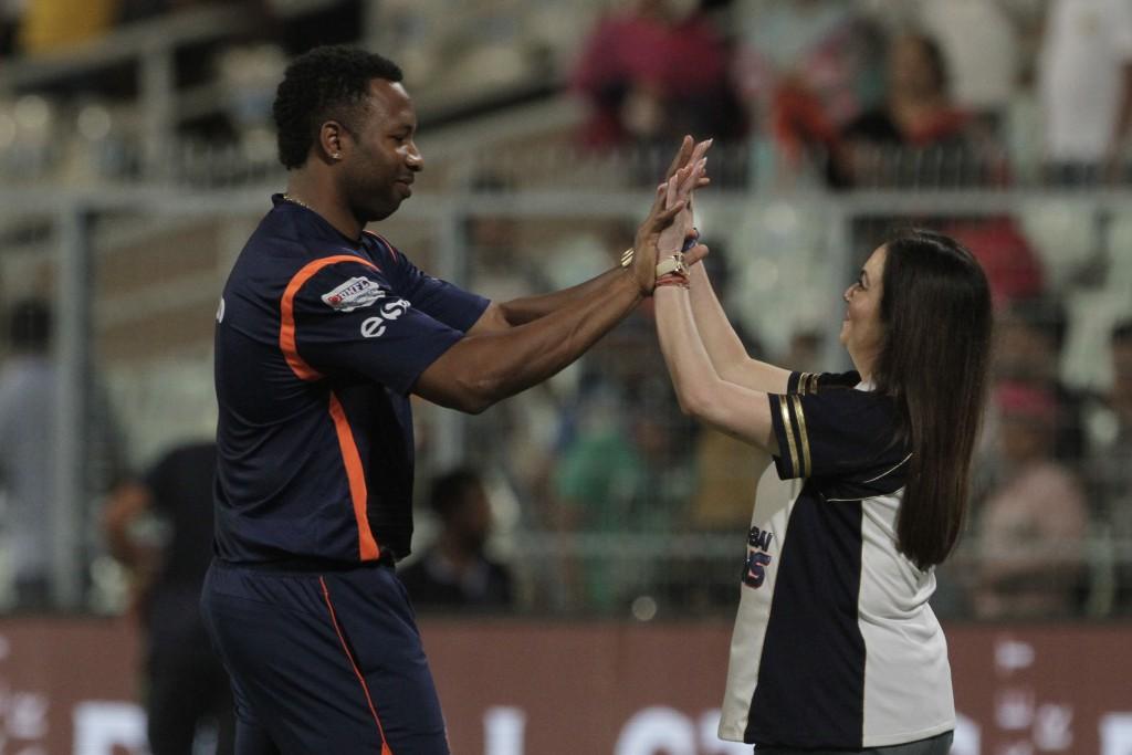 Mumbai Indians' team owner Nita Ambani celebrate their win over Kolkata Knight Riders with team player Kairon Pollard during the VIVO IPL cricket T20