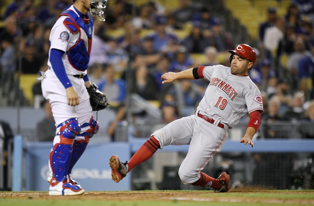 Cincinnati Reds' Joey Votto, right, scores on a double by Scooter Gennett as Los Angeles Dodgers catcher Yasmani Grandal stands at the plate during th...