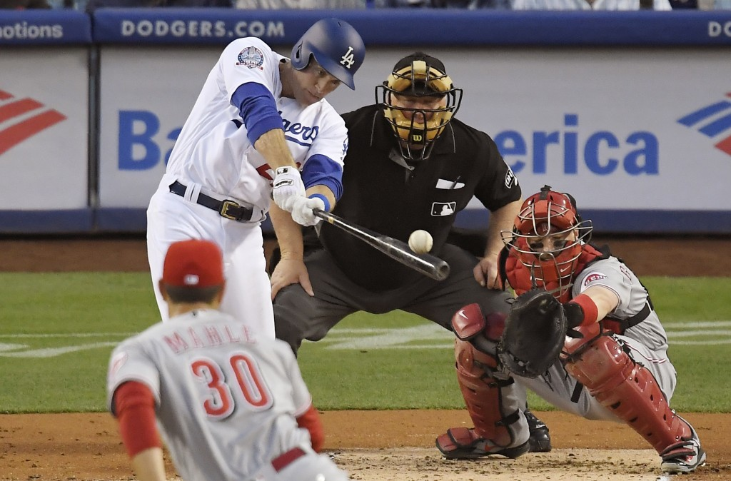Los Angeles Dodgers' Chase Utley hits an RBI single off Cincinnati Reds starting pitcher Tyler Mahle, front, during the first inning of a baseball gam...