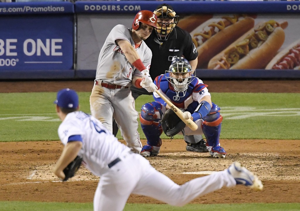Cincinnati Reds' Scooter Gennett hits a solo home run off Los Angeles Dodgers relief pitcher Daniel Hudson, foreground, during the eighth inning of a ...