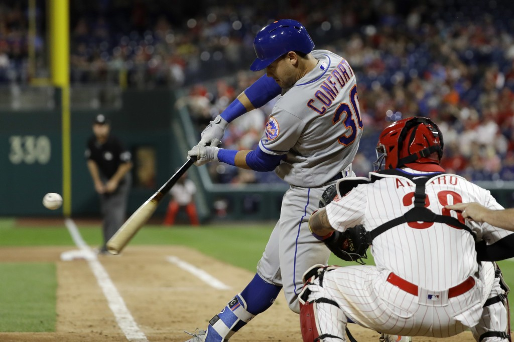 New York Mets' Michael Conforto, left, hits a two-run home run off Philadelphia Phillies relief pitcher Hector Neris during the ninth inning of a base...