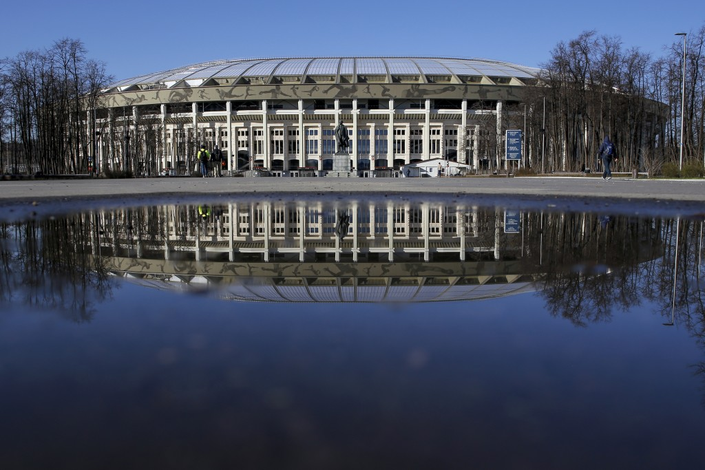 In this photo taken on Monday, April 23, 2018, the World Cup Luzhniki stadium is reflected in a puddle in Moscow, Russia. (AP Photo/Pavel Golovkin)
