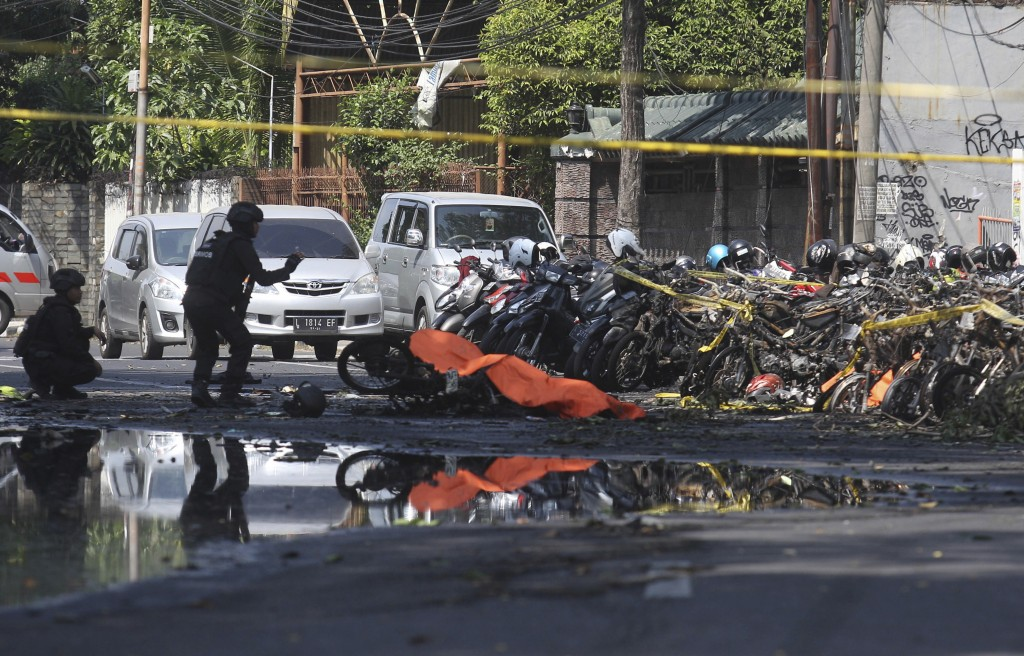 Members of police bomb squad inspect wreckage of motorcycles at the site where an explosion went off outside a church in Surabaya, East Java, Indonesi...