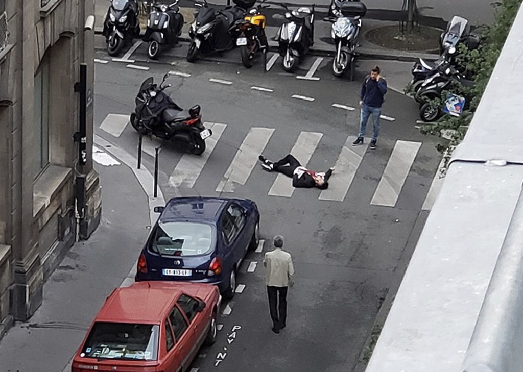 An unidentified man covered in blood lays on a street in Paris Saturday May 12, 2018, as two people look at him. The image was taken by a bystander wh...