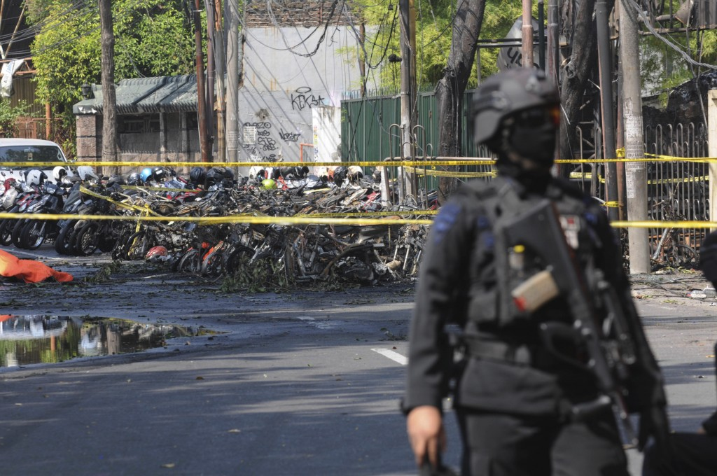 A police officer stands guard near the site where an explosion went off outside a church in Surabaya, East Java, Indonesia, Sunday, May 13, 2018. Mult...