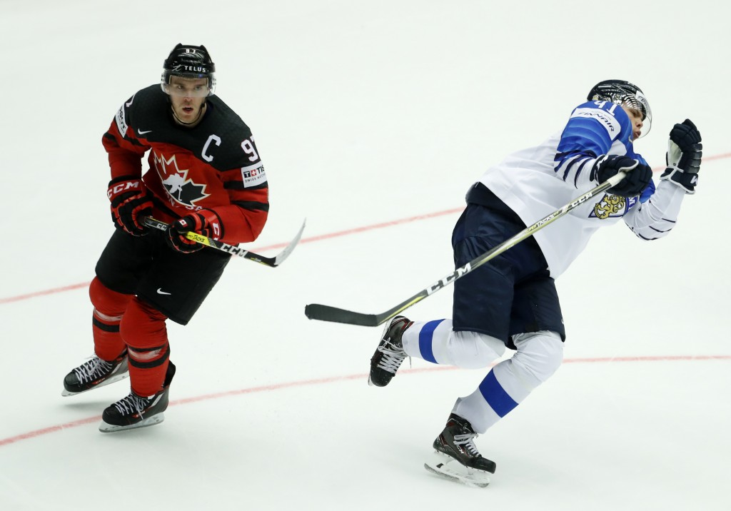 Canada's Connor McDavid, left, fouls Finland's Miro Heiskanen, right, during the Ice Hockey World Championships group B match between Canada and Finla...