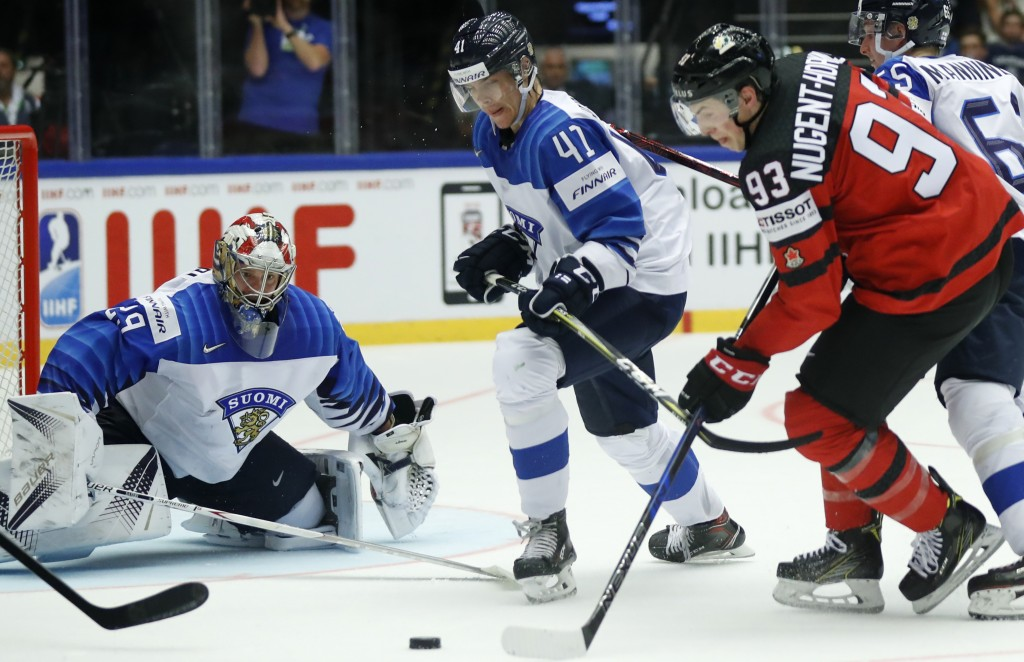 Finland's Miro Heiskanen, center, and Finland's goalkeeper Harri Sateri, left, try to stop Canada's Ryan Nugent-Hopkins, right, during the Ice Hockey ...