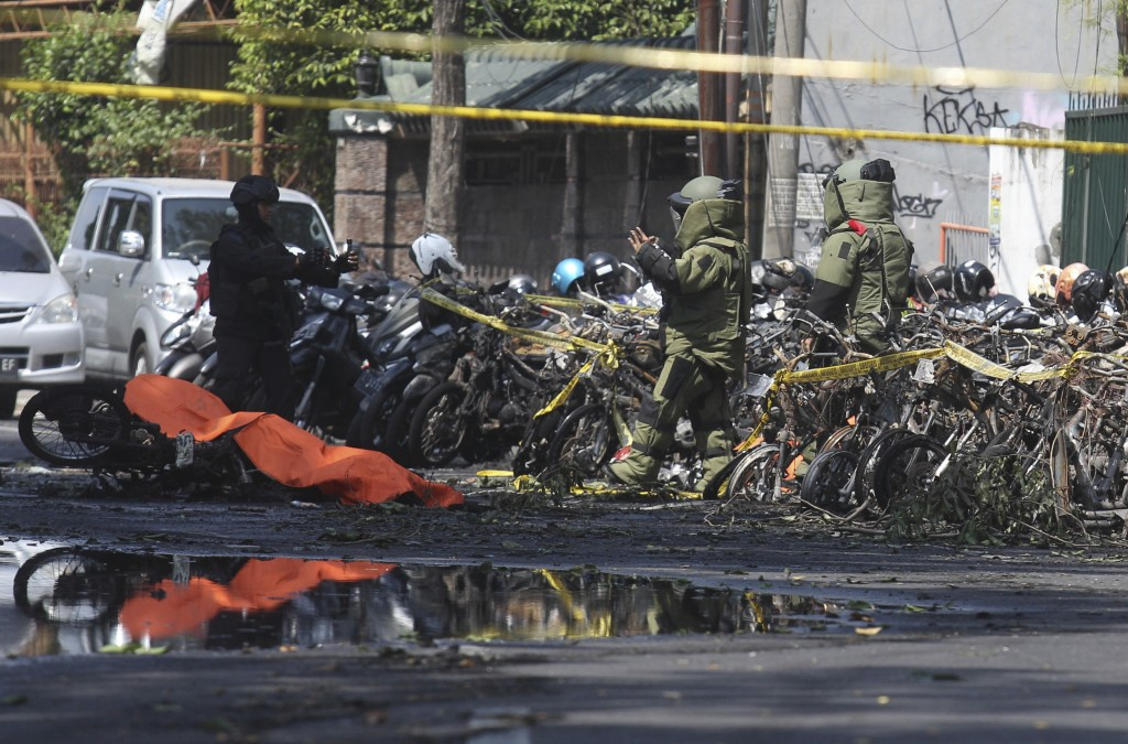 In this Sunday, May 13, 2018, file photo, members of police bomb squad inspect the wreckage of motorcycles at the site where an explosion went off out