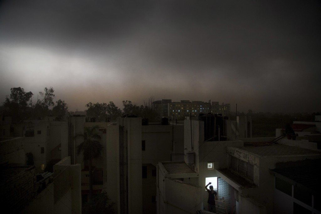 In this Sunday, May 13, 2018, file photo, an Indian man stands on the balcony of his apartment during a suddens storm accompanied by rain  in New Delh