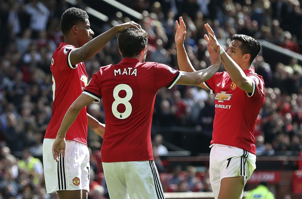 Manchester United's Marcus Rashford, left, celebrates with teammates Juan Mata, center, and Alexis Sanchez after scoring his side's first goal during
