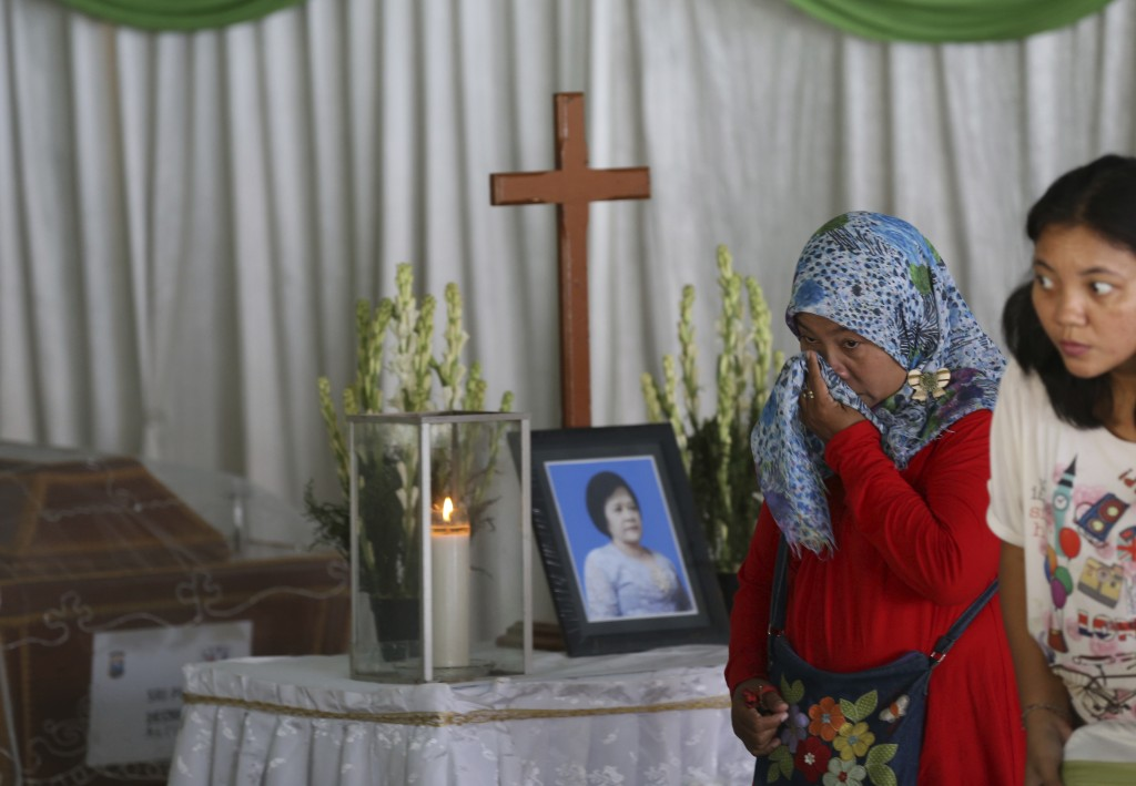 A Muslim woman weeps during the wake for Sri Pudji Astutik, one of the victims of Sunday's church attacks, at a funeral home in Surabaya, East Java, I...