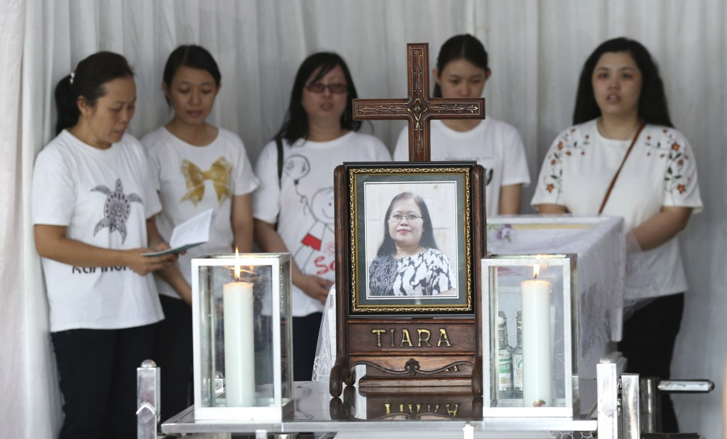 Family members pray during the wake for Marta Djumani, one of the victims of Sunday's church attacks, at a funeral home in Surabaya, East Java, Indone...
