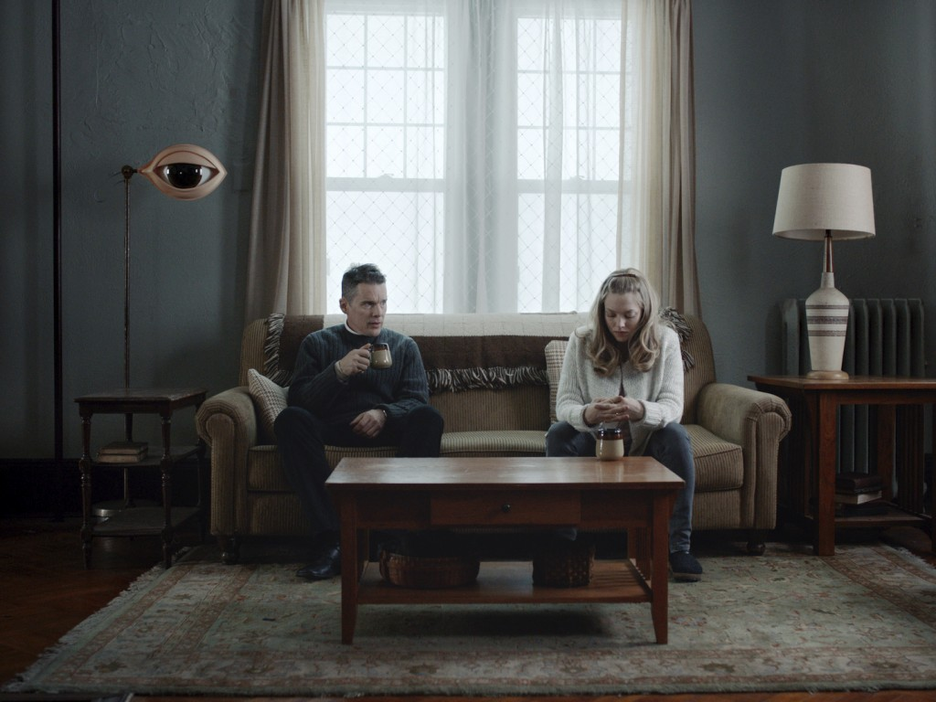 """This image released by A24 shows Ethan Hawke, left, and Amanda Seyfriend in a scene from """"First Reformed."""" (A24 via AP)"""