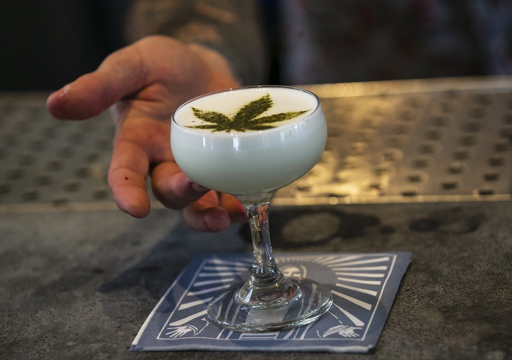 In this April 19, 2018, photo Maxwell Reis, beverage director serves a drink containing Cannabidol CBD extract with a marijuana leaf motif at the Grac