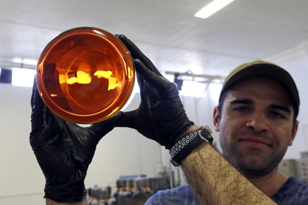 In this April 24, 2018 photo, Julian Cabrera, factory manager at New Earth Biosciences, holds up a large glass beaker to the light containing thick, g...