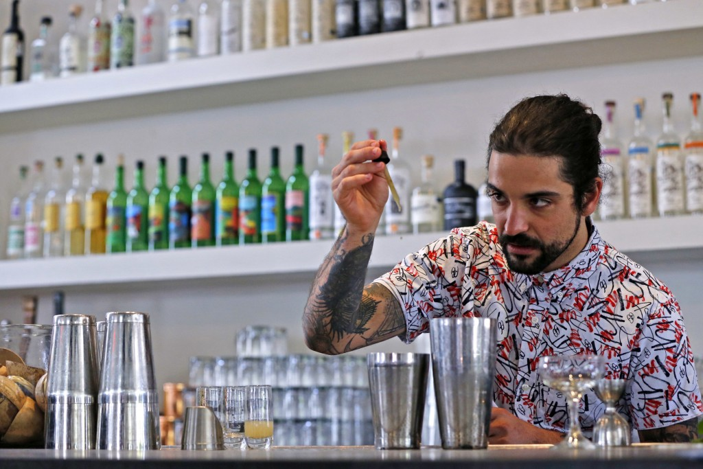 In this April 19, 2018, photo Maxwell Reis, beverage director adds a few drops of Cannabidol CBD extract to a mixed drink at the Gracias Madre restaur