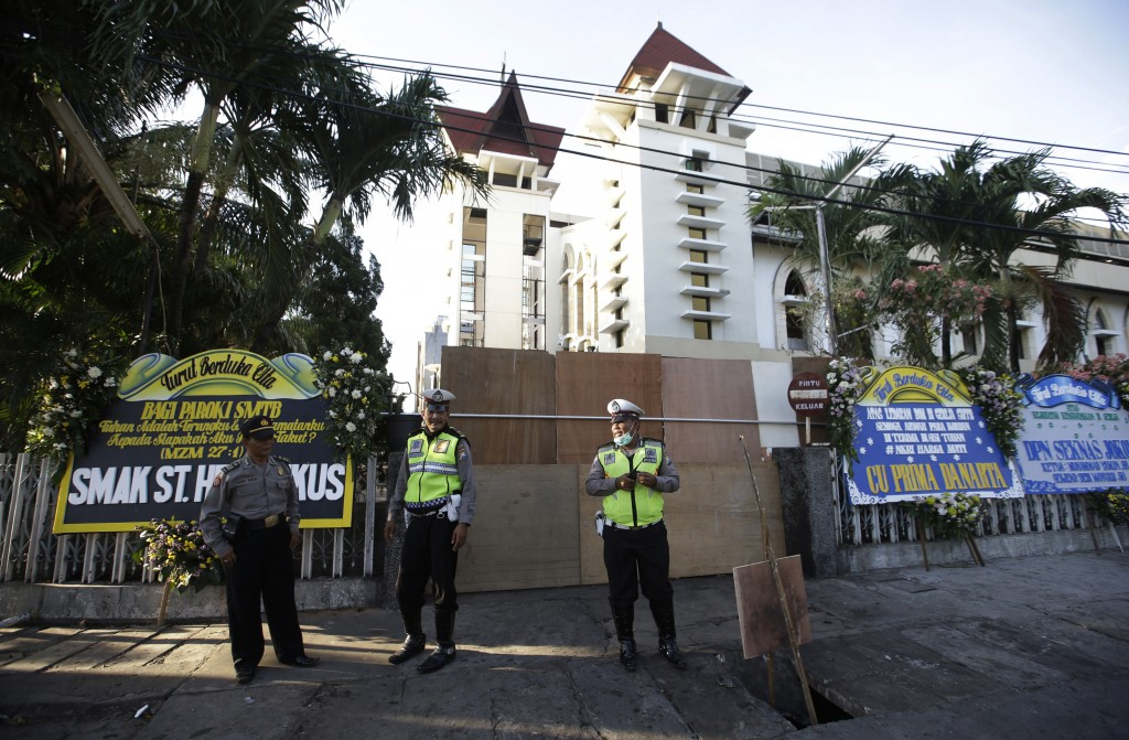 Police officers stand guard outside one of the churches attacked on Sunday, in Surabaya, East Java, Indonesia, Monday, May 14, 2018. The flurry of bom...