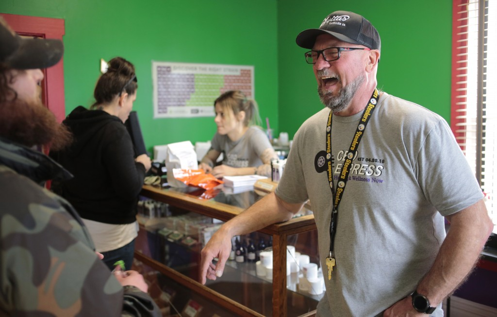 In this Friday, April 20, 2018 photo, Loren Kruesi, right, owner of CBD Express, talks with a customer during the store's grand opening in Salem, Ore.
