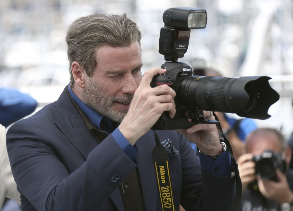 Actor John Travolta takes a picture with a press photographers camera during the photo call for the film 'Gotti' at the 71st international film festiv
