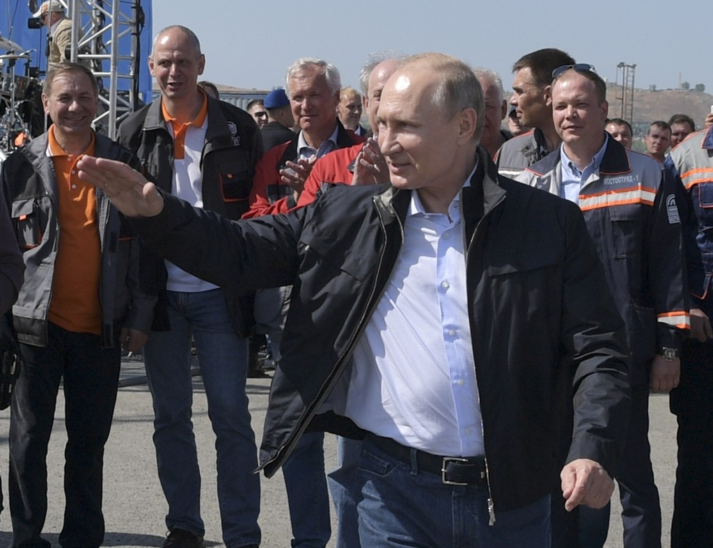 Russian President Vladimir Putin gestures while speaking to a group of workers after driving a truck to officially open the much-anticipated bridge li