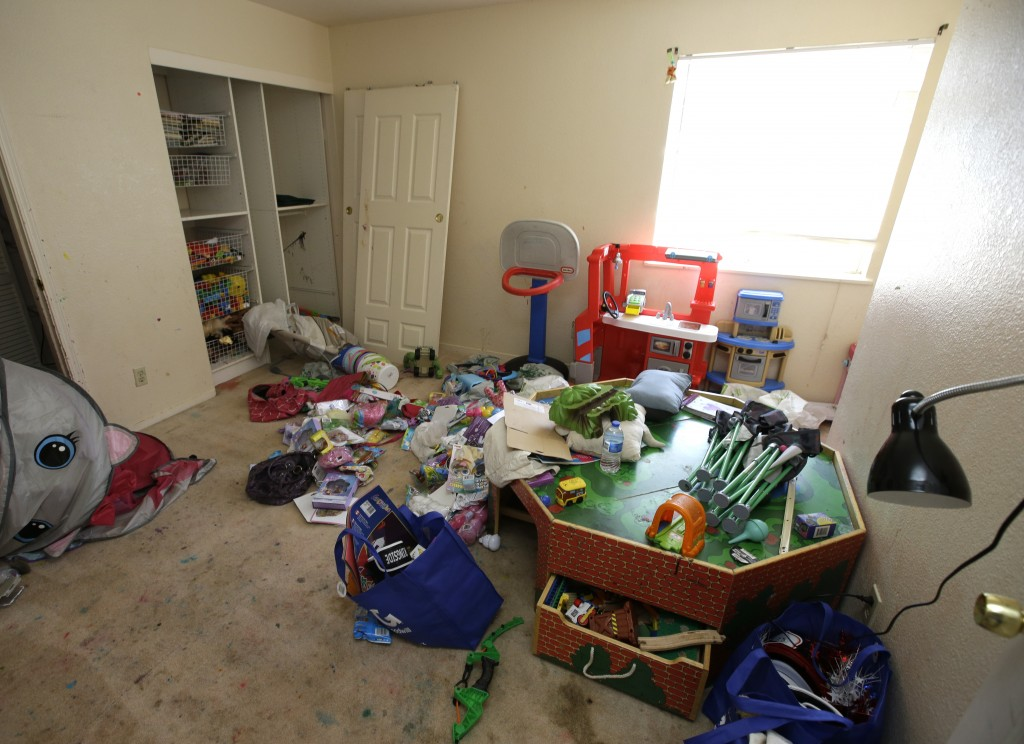 Toys and other items are strewn around one of the rooms of a home, Monday, May 14, 2018, where authorities removed 10 children and arrested their pare