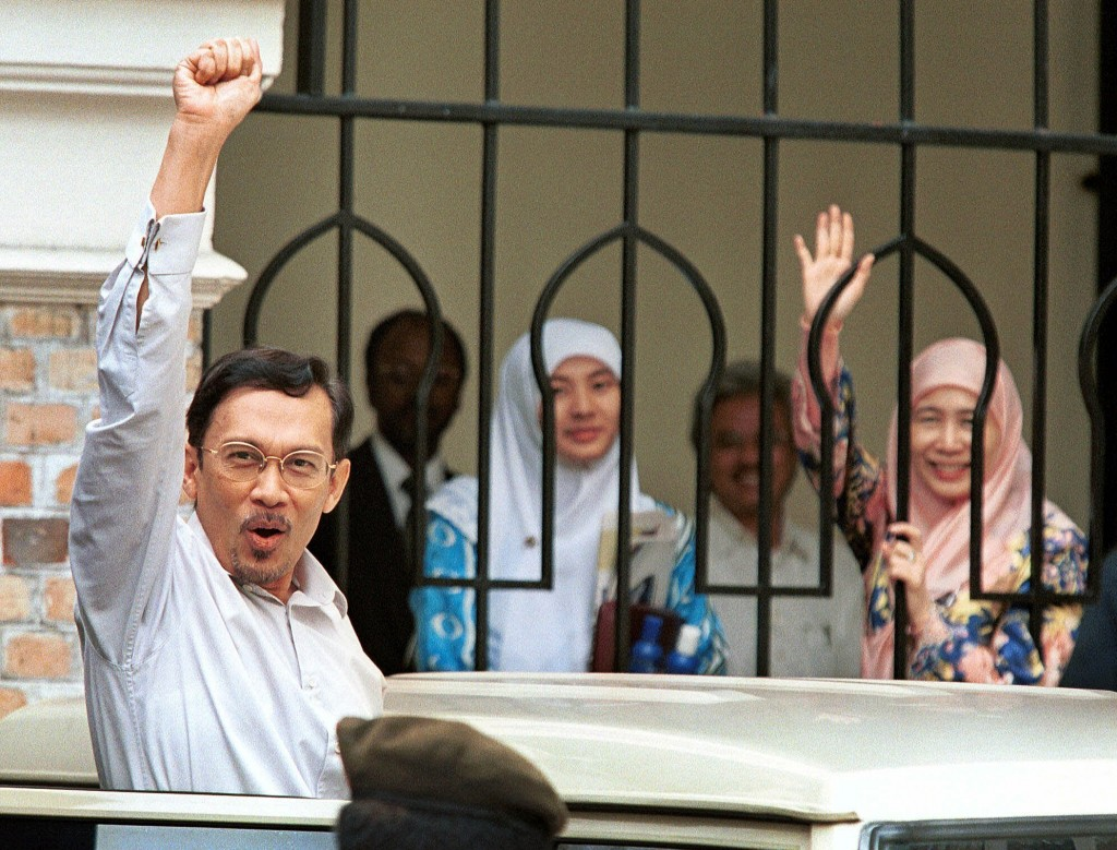 FILE - In this Nov. 12, 1999, file photo, Malaysian ousted Deputy Prime Minister Anwar Ibrahim raises his fist as his wife Wan Azizah, right, and his ...