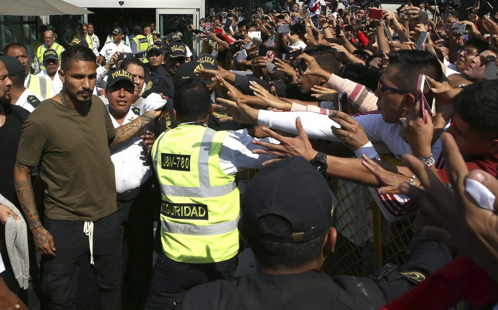 Peru captain Paolo Guerrero, left, is greeted by fans as he arrives in Lima, Peru, Tuesday, May 15, 2018. The global footballers' union wants FIFA's h